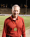Man wearing a medal on football field.