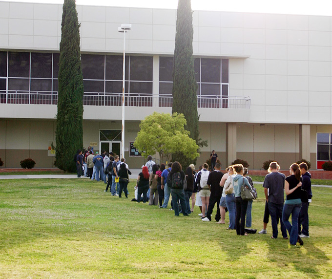 Multiple students stand in a long leading into the CSS building awaiting their turn to be seen.