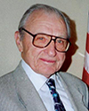 Man with glasses in suit and tie near a flag.