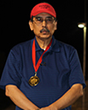 Man in dark shirt with a dark background wearing bright red cap and ribbon from medal that stand out.