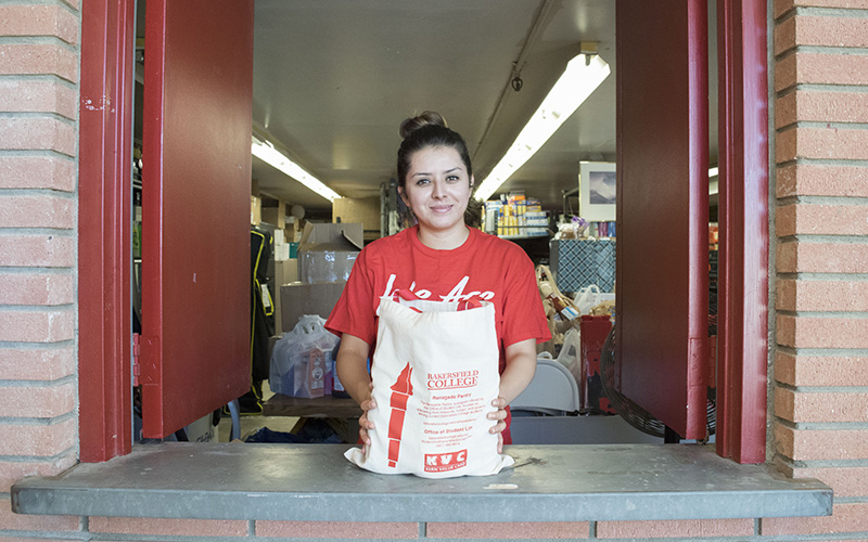 A student worker poses inside the Renegade Pantry window