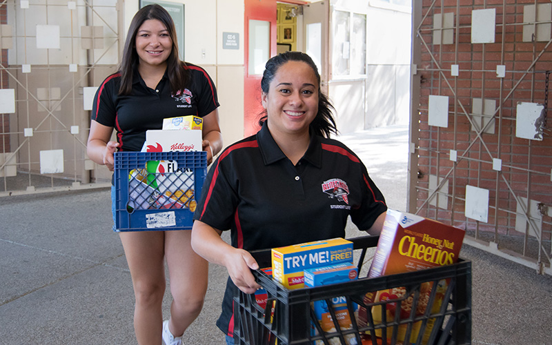 Two students deliver food to the Renegade Pantry