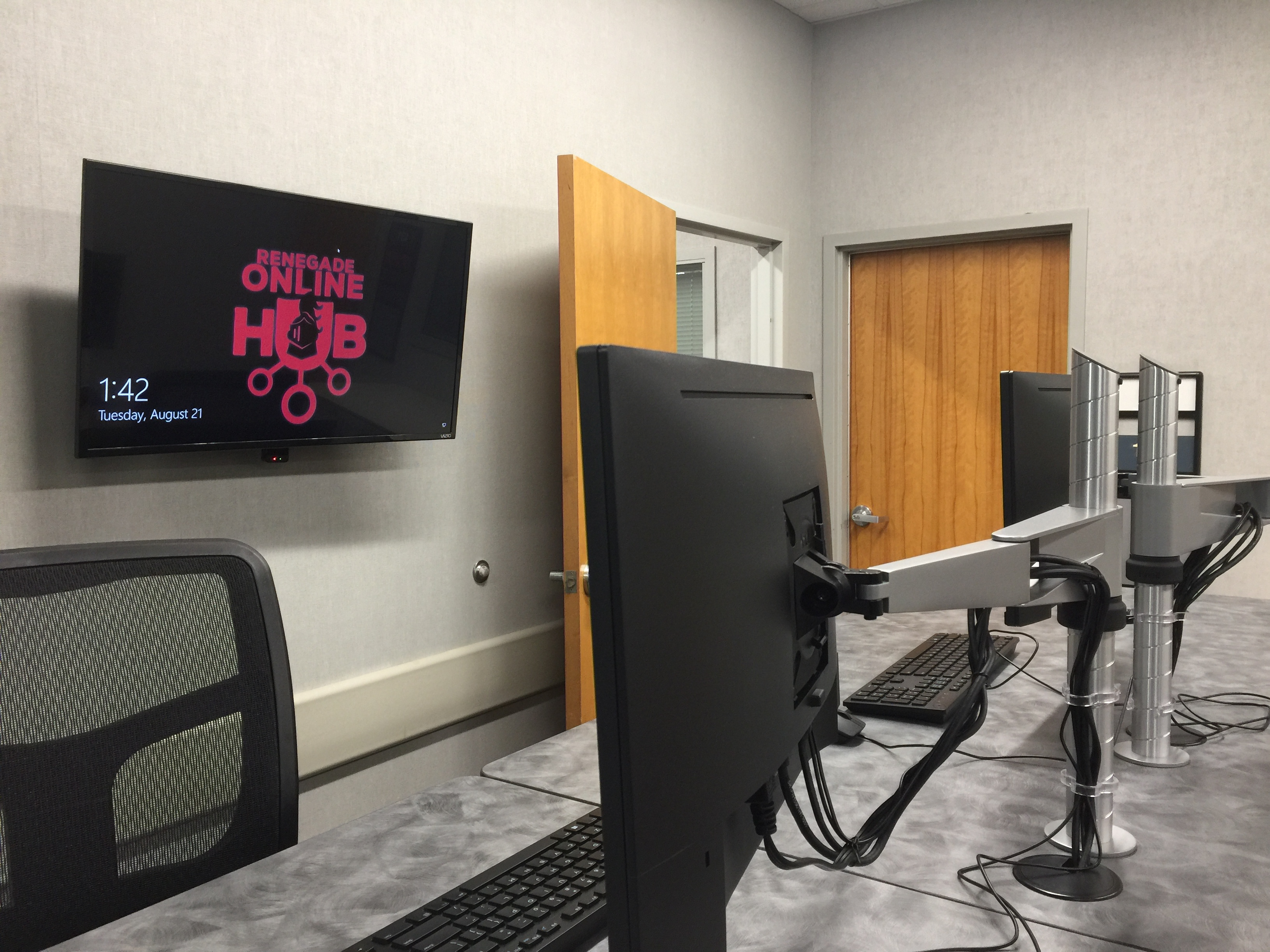 Desk with two monitors and a wall with a tv screen with Renegade Online Hub logo