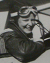 Woman in aviator jacket and goggles on head in open cockpit, black and white.