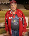 Older man in red jacket and cap with medal in football stadium.