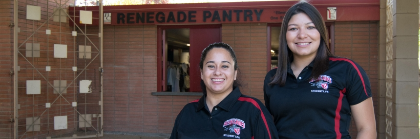 two students pose in front of the Renegade Pantry