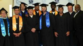Cerro Coso President Jill Board (left) and Dr. Lincoln Johnson (right) congratulate the first graduating class of students from the College's Prison Education Program in California City.